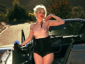 Erotic blonde is posing on the classic car