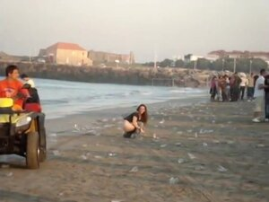 A fresh boozed girl pissing in public on the beach