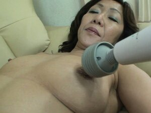 Asian granny sits back on the couch and vibrates her cunt, then he helps
