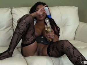 Gorgeous brunette cougar Priya Rai sits on the couch drilling her cunt with a dildo