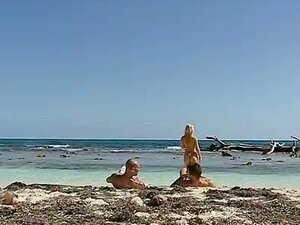 Blonde babe gets joined on the beach by two hard cocks