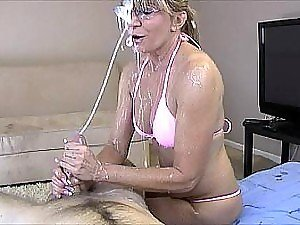 Horny blonde mature lady gives a handjob to a young guy