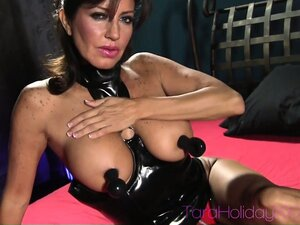 Wild brunette cougar in a sexy latex suit displays her fabulous tits and tight pussy