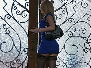 A beautiful blonde in a blue dress goes down on her co-worker's wang in the office
