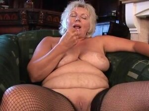 Solo granny in fishnets plays with her pussy
