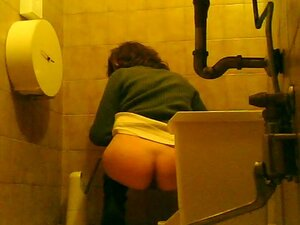 Cute girl with bubble booty is pissing in the toilet