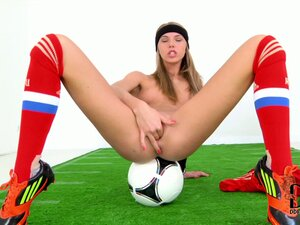 Soccer player sits on her ball as she sticks two fingers in her pussy