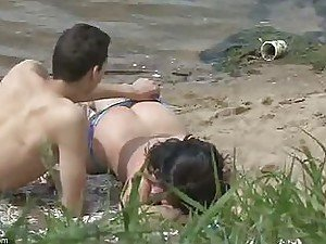 A voyeur spots a cute couple fooling around in the sand on a nudist beach